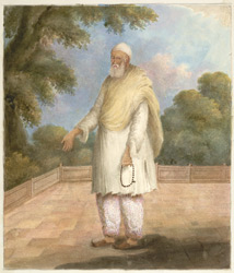 A maulvi holding a rosary and standing on a terrace